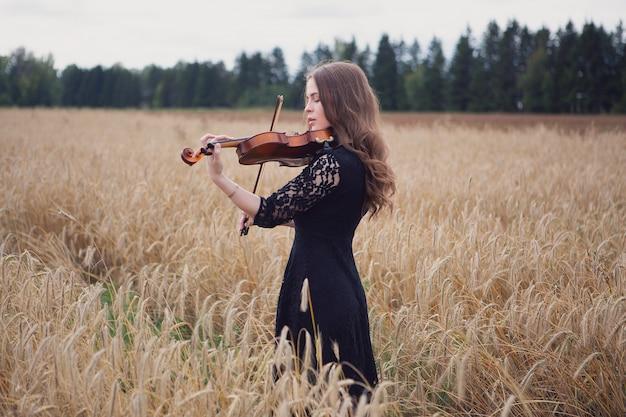 Eine junge geigerin spielt meisterhaft ihr instrument auf einem reifen weizenfeld Premium Fotos
