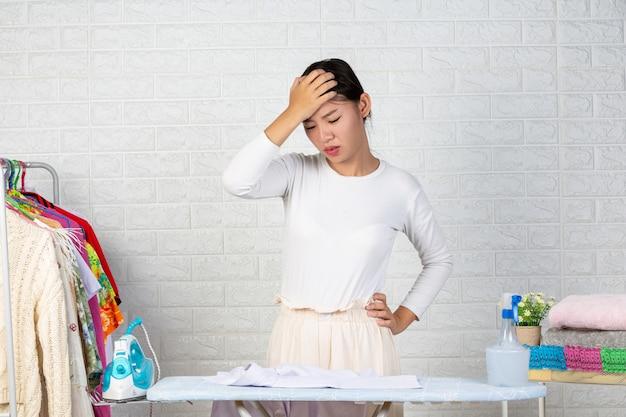 Eine junge hausfrau, die sich mit ihrem bügeln auf einem weißen backstein langweilt. Kostenlose Fotos
