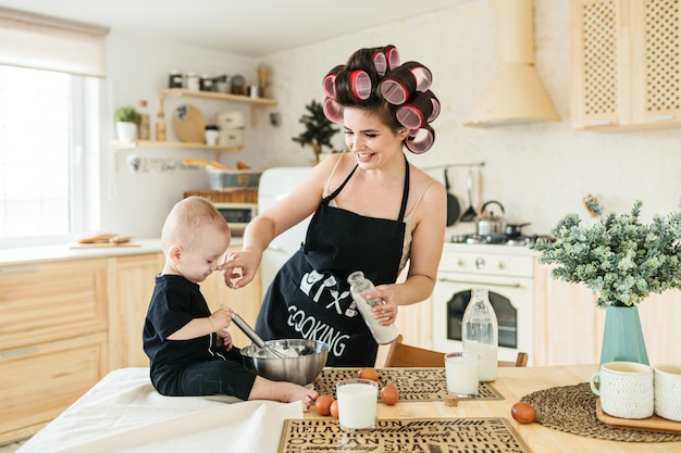 Eine junge mutter mit schürze und lockenwicklern bereitet mit ihrem kleinen kind in der küche eine geburtstagstorte zu Premium Fotos