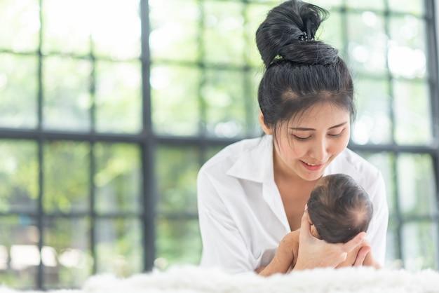 Eine junge mutter trägt ein baby Premium Fotos
