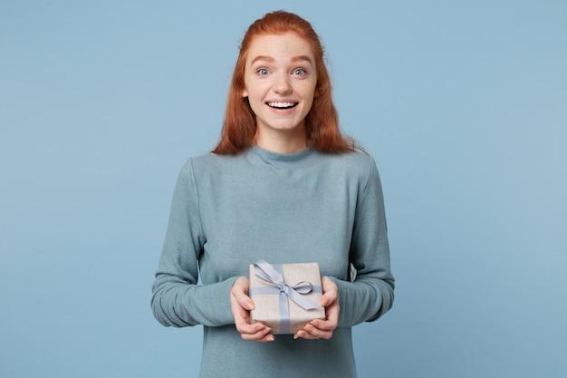 Eine junge rothaarige frau erhielt ein verpacktes geschenk, das mit einem blauen band gebunden war und es lächelnd in den händen hielt Kostenlose Fotos