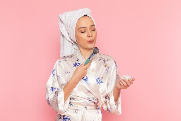 Eine junge schöne dame der vorderansicht im bademantel, der make-up tut Kostenlose Fotos