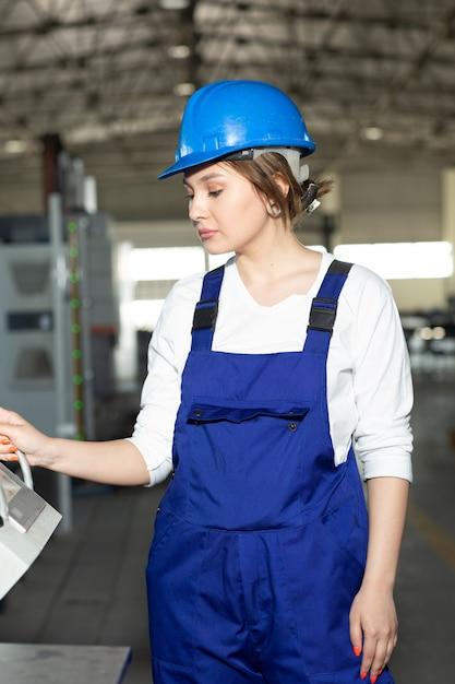 Eine junge schöne dame der vorderansicht im blauen bauanzug und in den helm, die maschinen im hangar steuern, die während der architektur des tagesgebäudes arbeiten Kostenlose Fotos