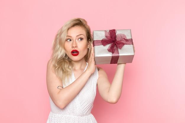 Eine junge schöne dame der vorderansicht im weißen kleid, die geschenkbox hält Kostenlose Fotos