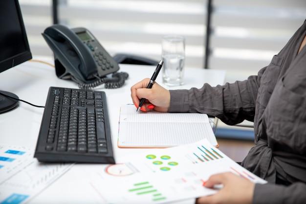 Eine junge schöne geschäftsfrau der vorderansicht, die an ihrem pc auf dem tisch zusammen mit telefon und grafiken arbeitet, notiert notizen jobaktivitäten technologie Kostenlose Fotos
