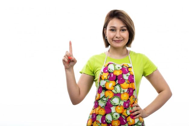 Eine junge schöne hausfrau der vorderansicht des bunten umhangs des grünen hemdes, der mit dem erhöhten finger lächelnd auf der weiblichen küche des weißen hintergrundhauses posiert Kostenlose Fotos