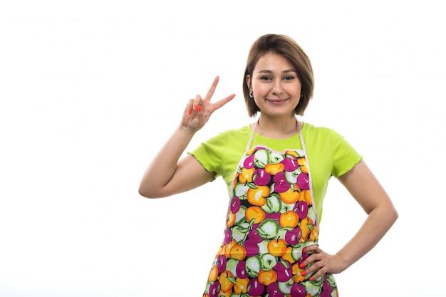 Eine junge schöne hausfrau der vorderansicht des bunten umhangs des grünen hemdes, der mit den erhabenen fingern posiert, die auf der weiblichen küche des weißen hintergrundhauses lächeln Kostenlose Fotos