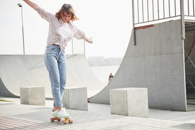 Eine junge sportfrau, die in einem park auf einem skateboard reitet. Kostenlose Fotos