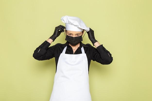 Eine junge weibliche köchin der vorderansicht im weißen hemd des weißen hemdes des weißen hemdes, das in den schwarzen handschuhen aufwirft, die schwarze maske aufwirft Kostenlose Fotos