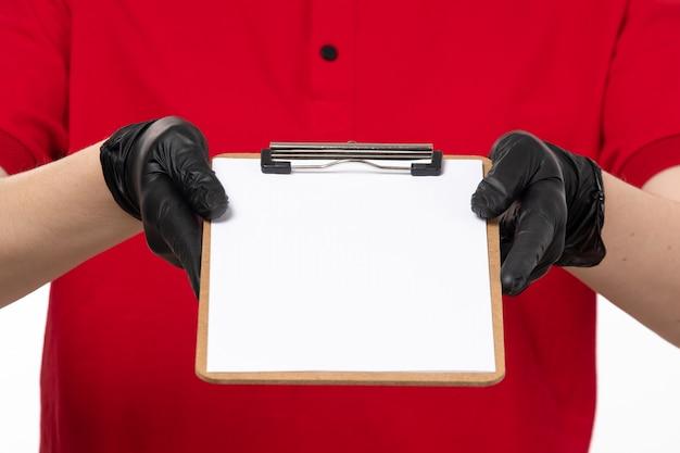Eine junge weibliche kurierin der vorderansicht im roten hemd und in den schwarzen handschuhen, die papiernotiz halten Kostenlose Fotos