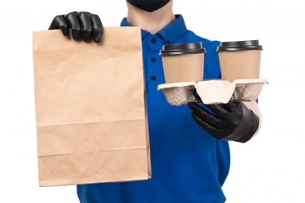 Eine junge weibliche kurierin der vorderansicht in der blauen einheitlichen schwarzen maske und in den handschuhen, die kaffeetassen und paket halten Kostenlose Fotos