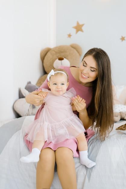 Eine kaukasische mutter legt ihre einjährige tochter auf den schoß und sieht sie im kinderzimmer des hauses an und lächelt Premium Fotos
