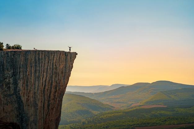 Eine kleine figur eines touristen mit offenen armen, der am rand einer klippe in den sommerbergen steht Premium Fotos
