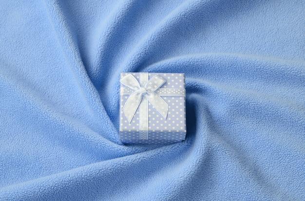 Eine kleine geschenkbox in blau mit kleiner schleife liegt auf einer decke Premium Fotos