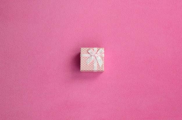 Eine kleine geschenkbox in rosa mit einer kleinen schleife liegt auf einer decke aus weichem und pelzigem hellrosa fleece. verpackung für ein geschenk an ihre schöne freundin Premium Fotos