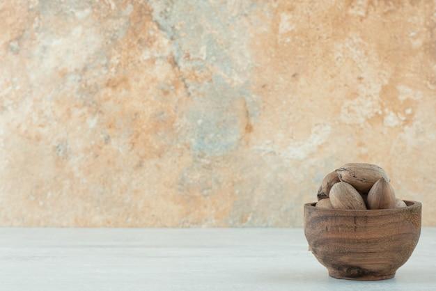Eine kleine hölzerne schüssel nüsse auf weißem hintergrund. hochwertiges foto Kostenlose Fotos