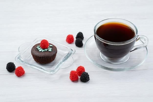 Eine köstliche braune vorderansicht zusammen mit frischen beeren und einer tasse tee auf weißen, bonbonfarbenen süßigkeiten Kostenlose Fotos