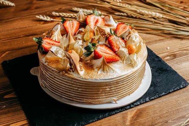Eine köstliche geburtstagstorte der vorderansicht, die mit den leckeren runden erdbeeren innerhalb des weißen kekses des weißen plattengeburtstags auf dem braunen hintergrund verziert wird Kostenlose Fotos