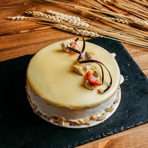 Eine köstliche geburtstagstorte der vorderansicht verziert leckere runde innerhalb des süßen kekses des weißen plattengeburtstags auf dem braunen hintergrund Kostenlose Fotos