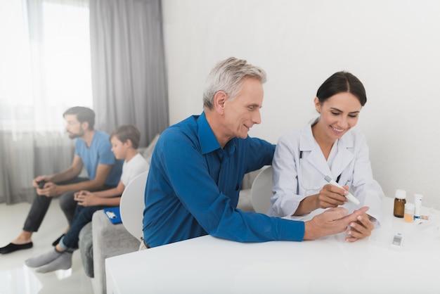 Eine krankenschwester entnimmt mit einem vertikutierer eines alten mannes eine blutprobe Premium Fotos
