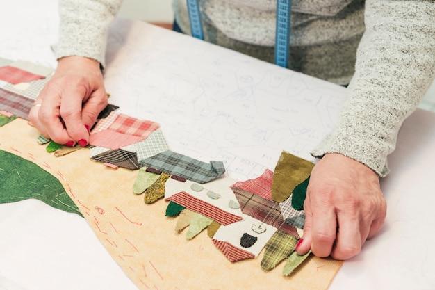 Eine kreative junge frau, die gewebepatchworklandschaft auf papier schafft Kostenlose Fotos