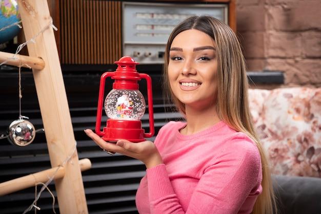 Eine lächelnde frau, die eine rote weihnachtslampe hält. hochwertiges foto Kostenlose Fotos