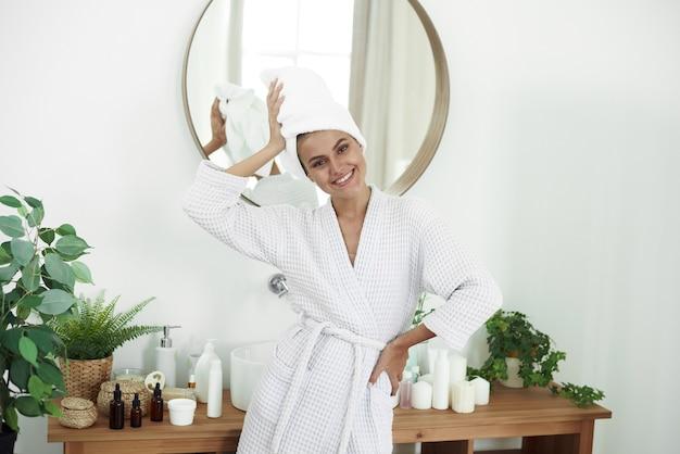 Eine lächelnde junge frau ist gerade aus der dusche gekommen und steht im badezimmer. hautpflege, morgenroutine. Premium Fotos