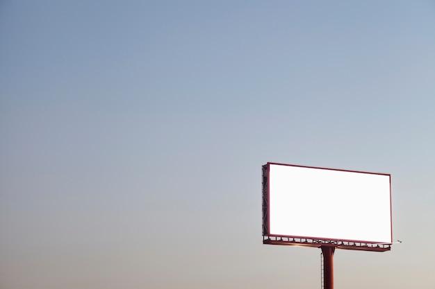 Eine leere werbungsanschlagtafel im freien gegen blauen himmel Kostenlose Fotos