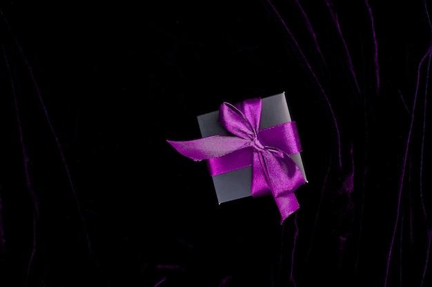 Eine luxuriöse schwarze geschenkbox mit violettem band Premium Fotos