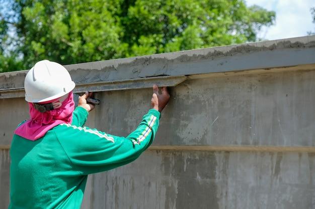 Eine maurerarbeitskraft, die zement auf betonmauer im heißen wetter an der baustelle vergipst. Premium Fotos