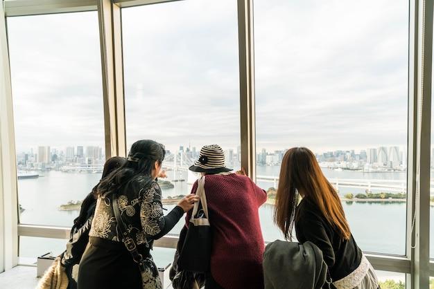 Eine menge von touristen und einheimischen genießen die aussicht auf die tokyo bay von odaiba an einem bewölkten herbst nachmittag. Kostenlose Fotos