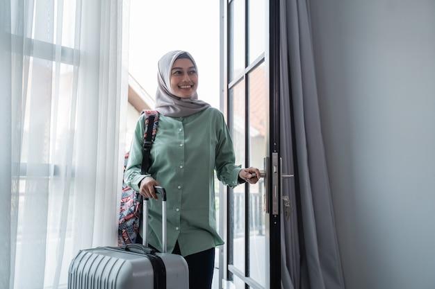 Eine muslimische reisende öffnete mit ihrer tasche und ihrem koffer den eingang zur tür Premium Fotos