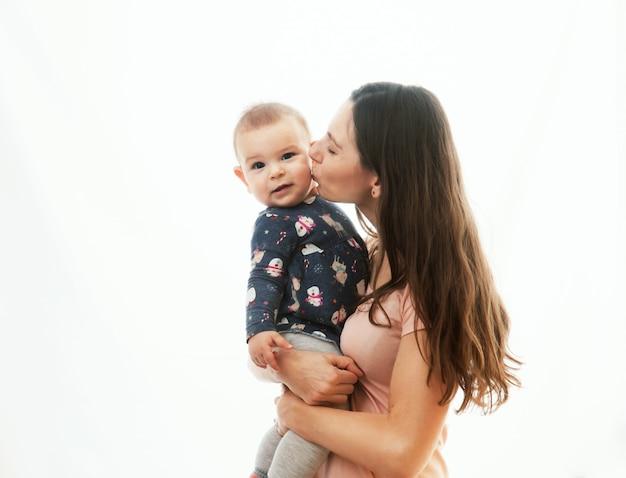 Eine mutter und ein baby, die zusammen auf weißem hintergrund verpfänden Premium Fotos