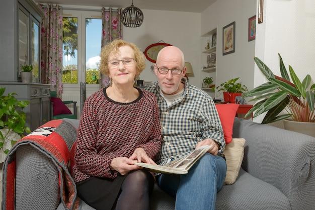 Eine mutter und ihr erwachsener sohn, die ein fotoalbum auf einem sofa betrachten Premium Fotos