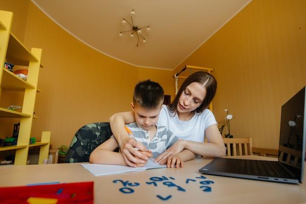Eine mutter und ihr kind lernen zu hause vor dem computer fernunterricht. bleib zu hause und trainiere. Premium Fotos