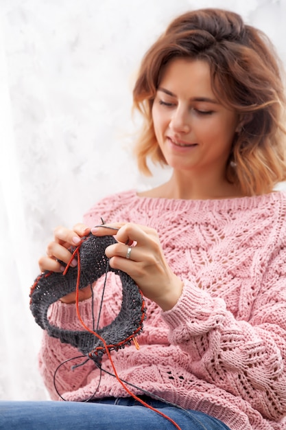 Eine nahaufnahme einer jungen frau in einer rosa wolljacke strickt mit stricknadeln aus natürlichen wollfäden Premium Fotos