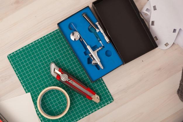 Eine nahaufnahme einer reihe von werkzeugen: ein papierschneidemesser, ein millimeterpapier. Premium Fotos