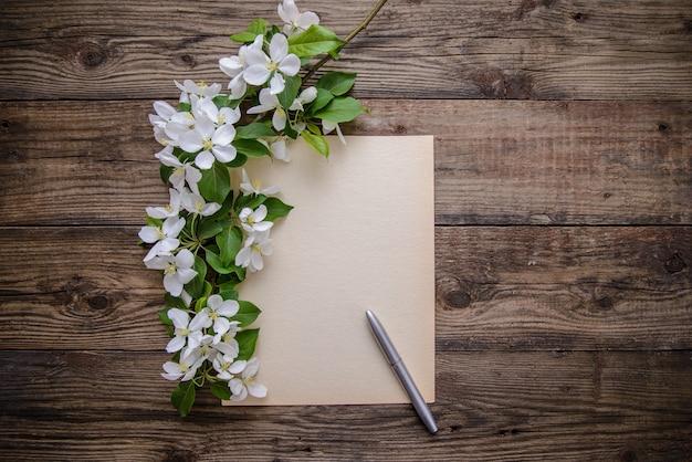 Eine niederlassung von apfelblüten, stift und papier bedecken auf hölzernem hintergrund Premium Fotos