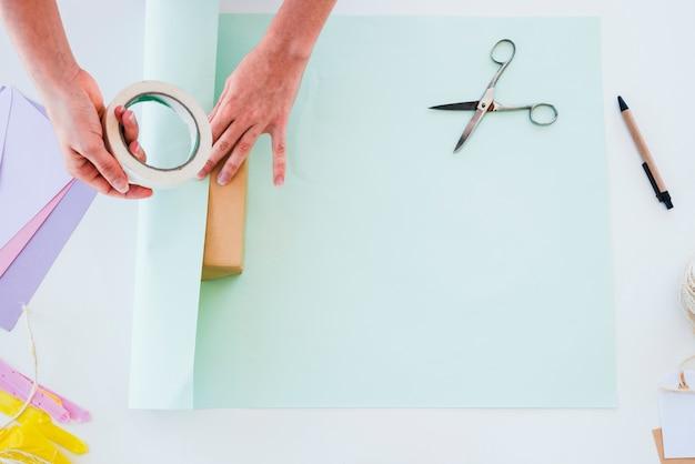 Eine obenliegende ansicht der hand der frau das papier auf geschenkbox über dem weißen schreibtisch haftend Kostenlose Fotos