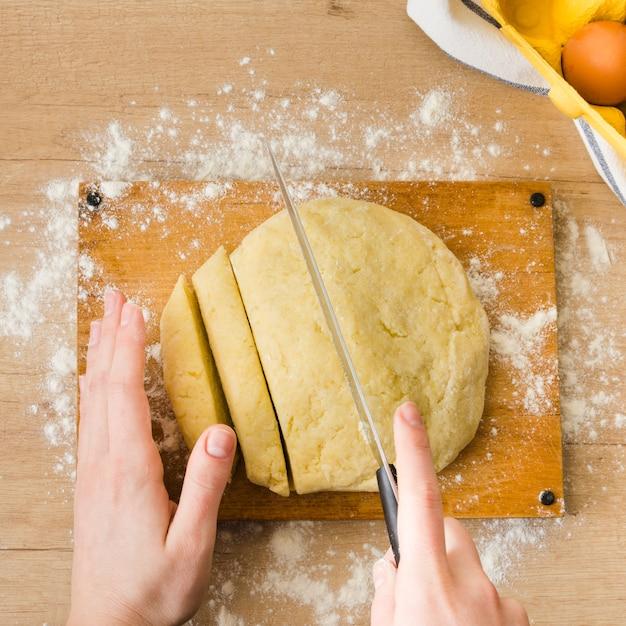 Eine obenliegende ansicht der hand der frau den teig für das zubereiten der italienischen gnocchiteigwaren auf holztisch schneiden Kostenlose Fotos