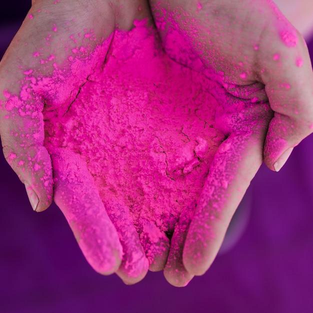 Eine obenliegende ansicht der hand des menschen rosa holi farbe halten Kostenlose Fotos