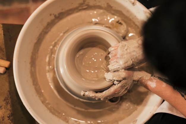 Eine obenliegende ansicht der hand des weiblichen töpfers, die ein tönernes glas auf der töpferscheibe herstellt Kostenlose Fotos