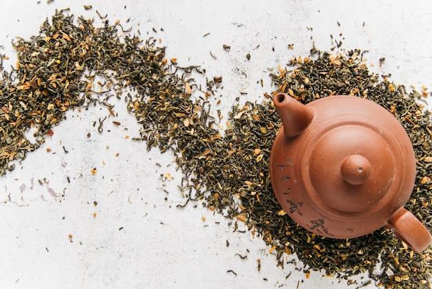 Eine obenliegende ansicht der lehmteekanne auf trockenen teekräutern über dem konkreten hintergrund Premium Fotos