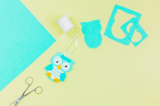 Eine obenliegende ansicht der papiereule mit threadspule und -schere auf gelbem hintergrund Kostenlose Fotos