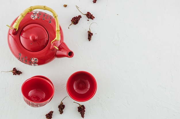 Eine obenliegende ansicht der roten traditionellen teeschale und -teekanne mit den kräutern lokalisiert auf weißem hintergrund Kostenlose Fotos