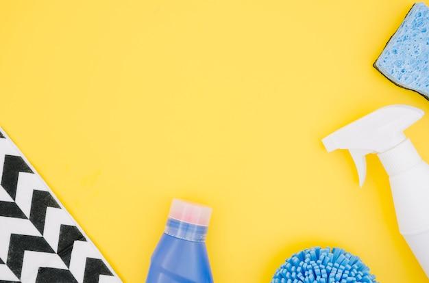 Eine obenliegende ansicht der sprühflasche und des schwammes auf gelbem hintergrund Kostenlose Fotos