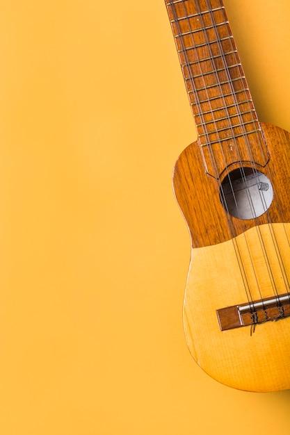 Eine obenliegende ansicht der ukulele auf gelbem hintergrund Kostenlose Fotos