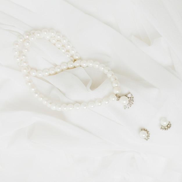 Eine obenliegende ansicht der weißen perlenhalskette und -ohrringe auf weißem schal Kostenlose Fotos