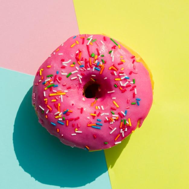 Eine obenliegende ansicht des donuts gegen bunten hintergrund Kostenlose Fotos