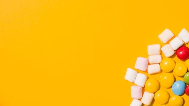 Eine obenliegende ansicht des eibisches und der bunten süßigkeiten auf gelbem hintergrund Kostenlose Fotos